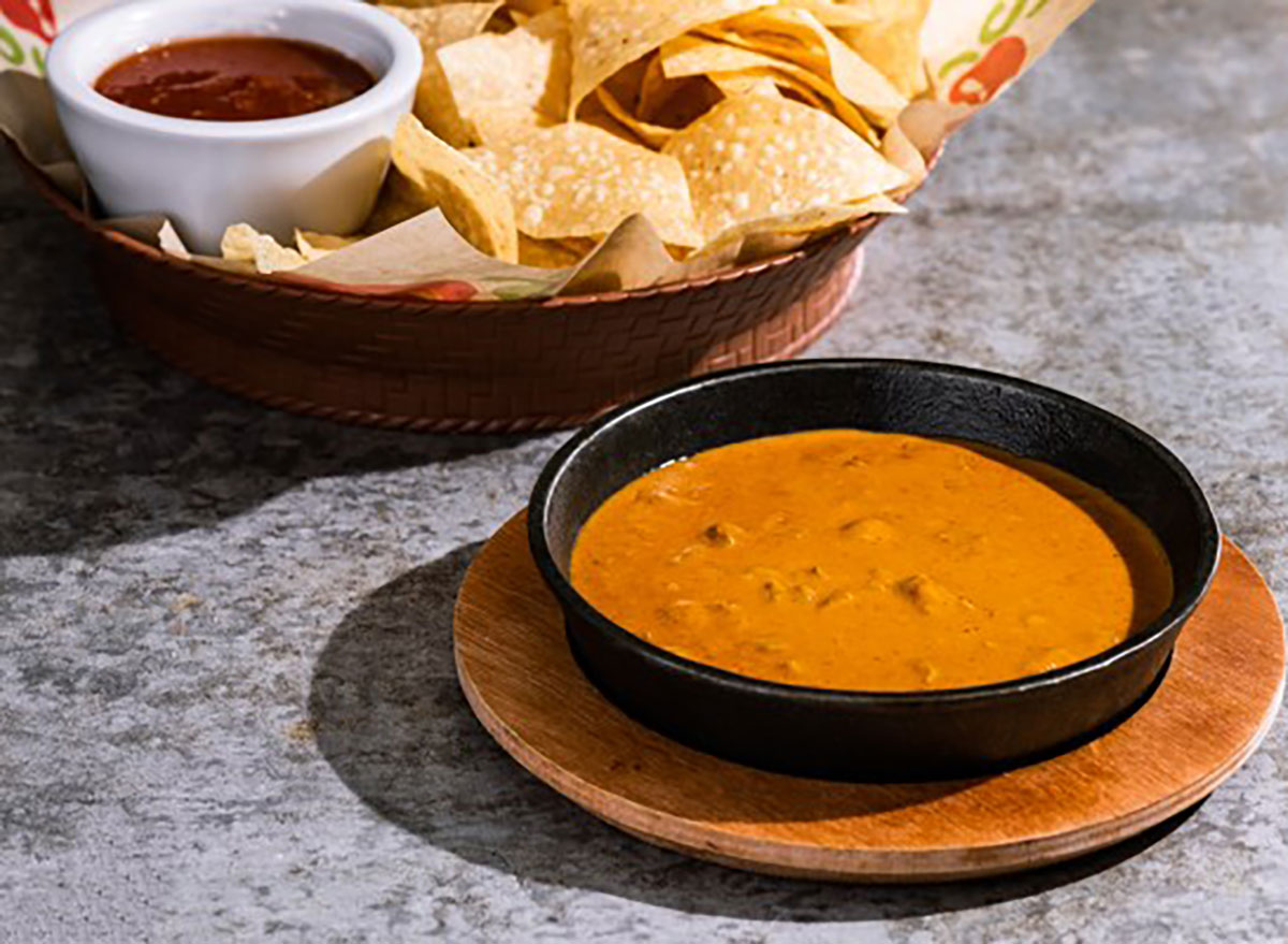 bowl of chilis skillet queso with basket of tortilla chips and salsa