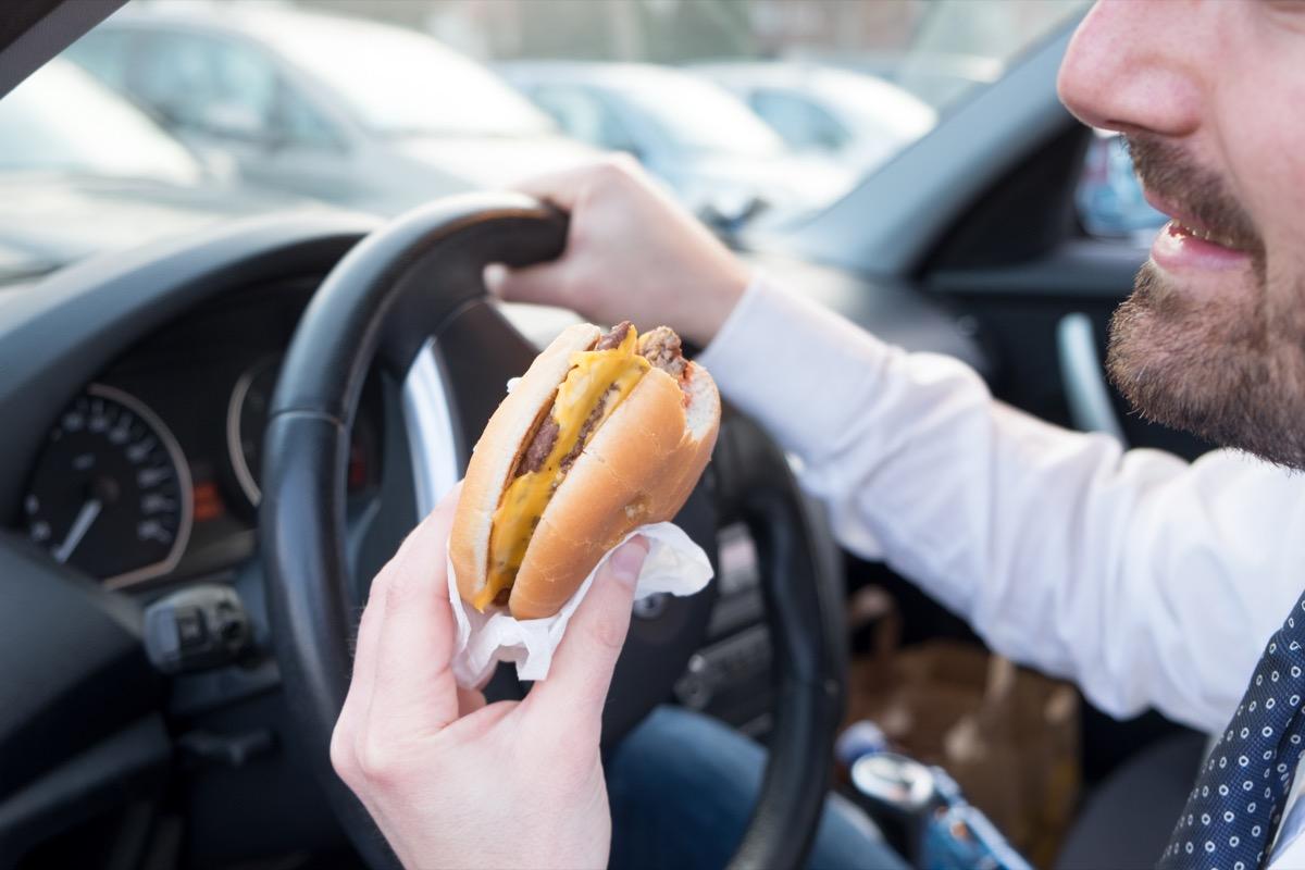 Man eating an hamburger while driving car