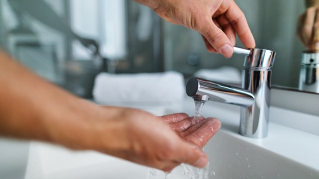 fingers under hot water out of a faucet of a sink