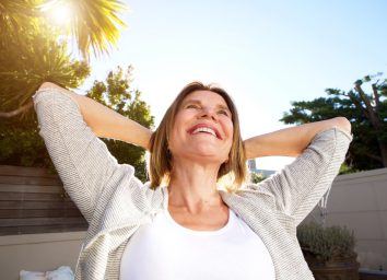happy older woman smiling with hands behind head