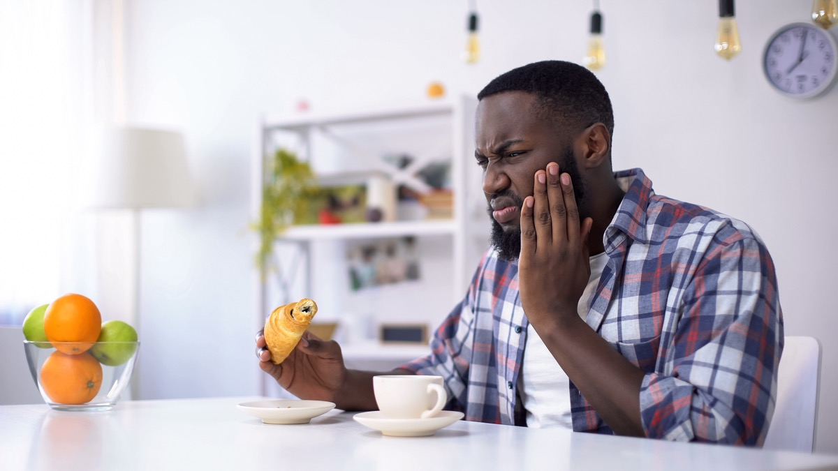 man feeling tooth ache from sweet food, eating croissant with coffee