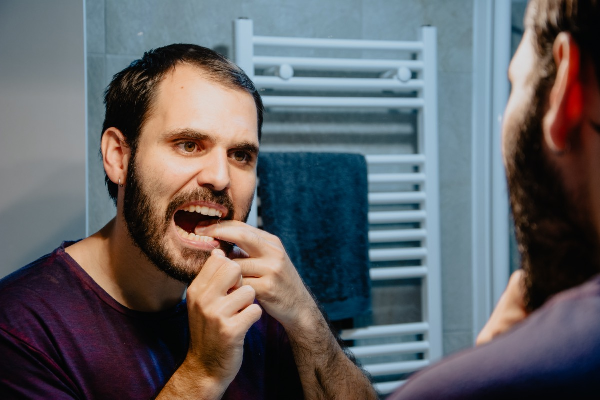 cleaning his teeth with dental floss and smiling while standing in front of the mirror