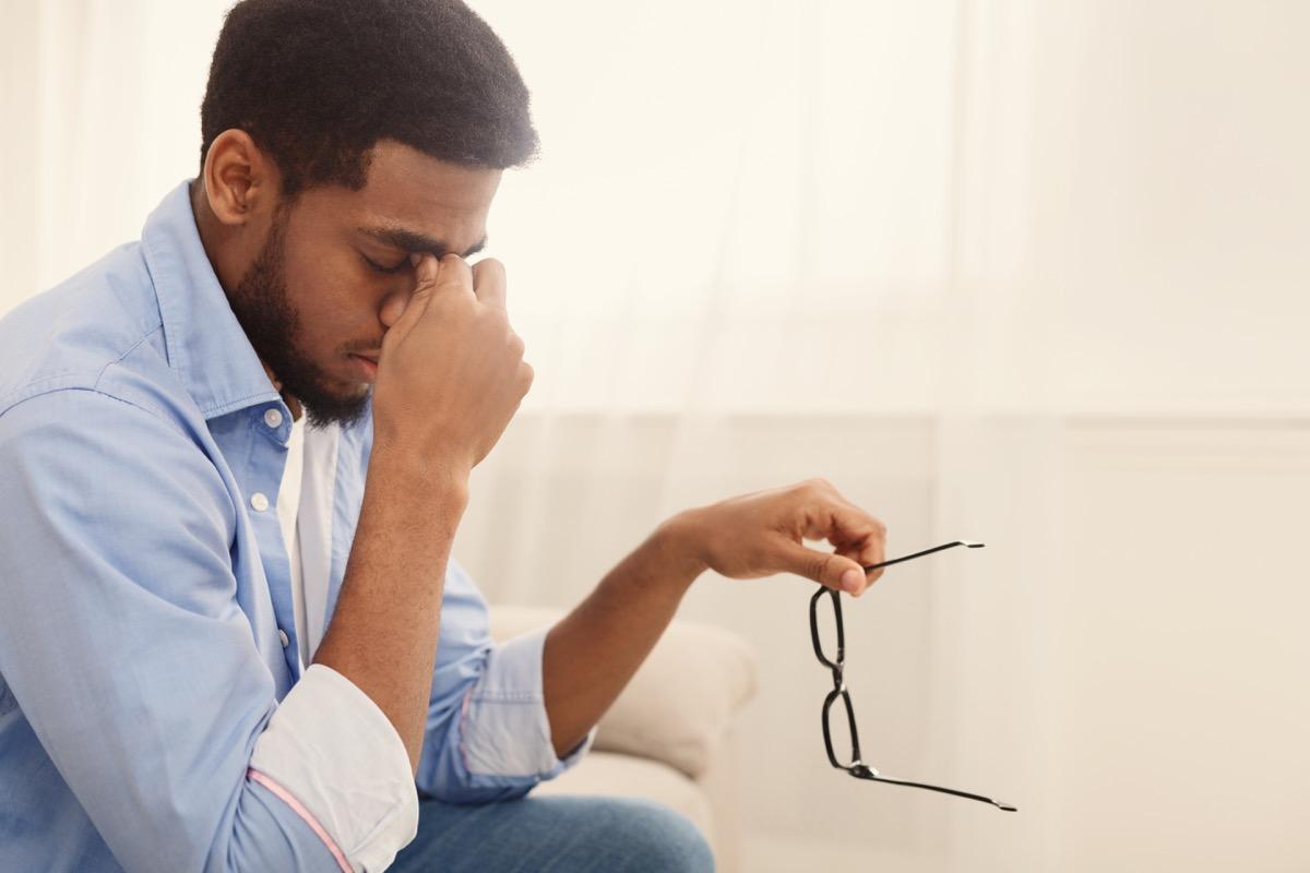 man massaging nose bridge, taking glasses off, having blurry vision or dizziness