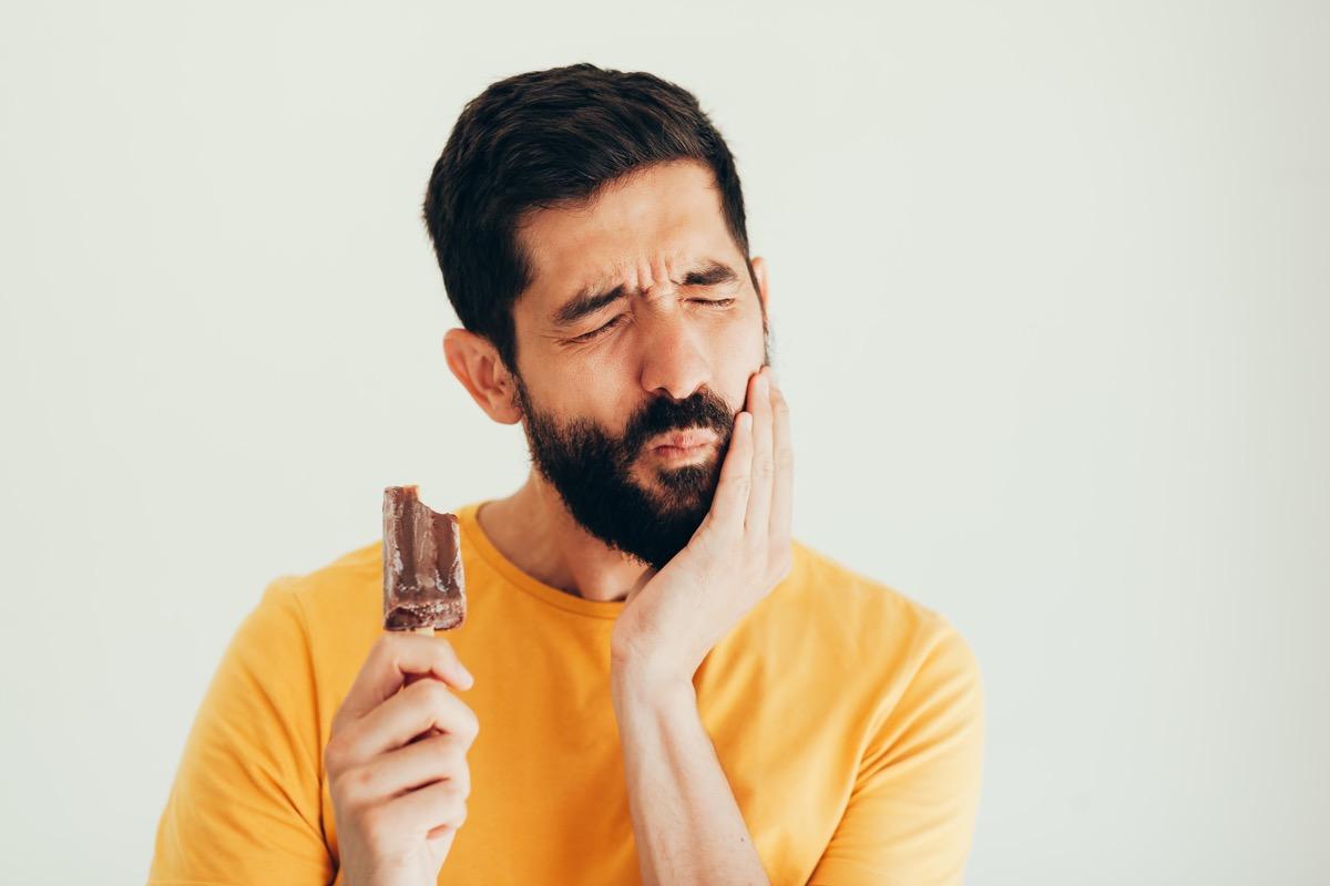 Man have sensitive teeth with ice
