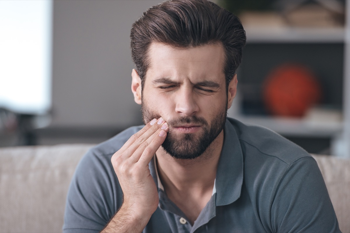 Toothache. Frustrated young man touching his cheek