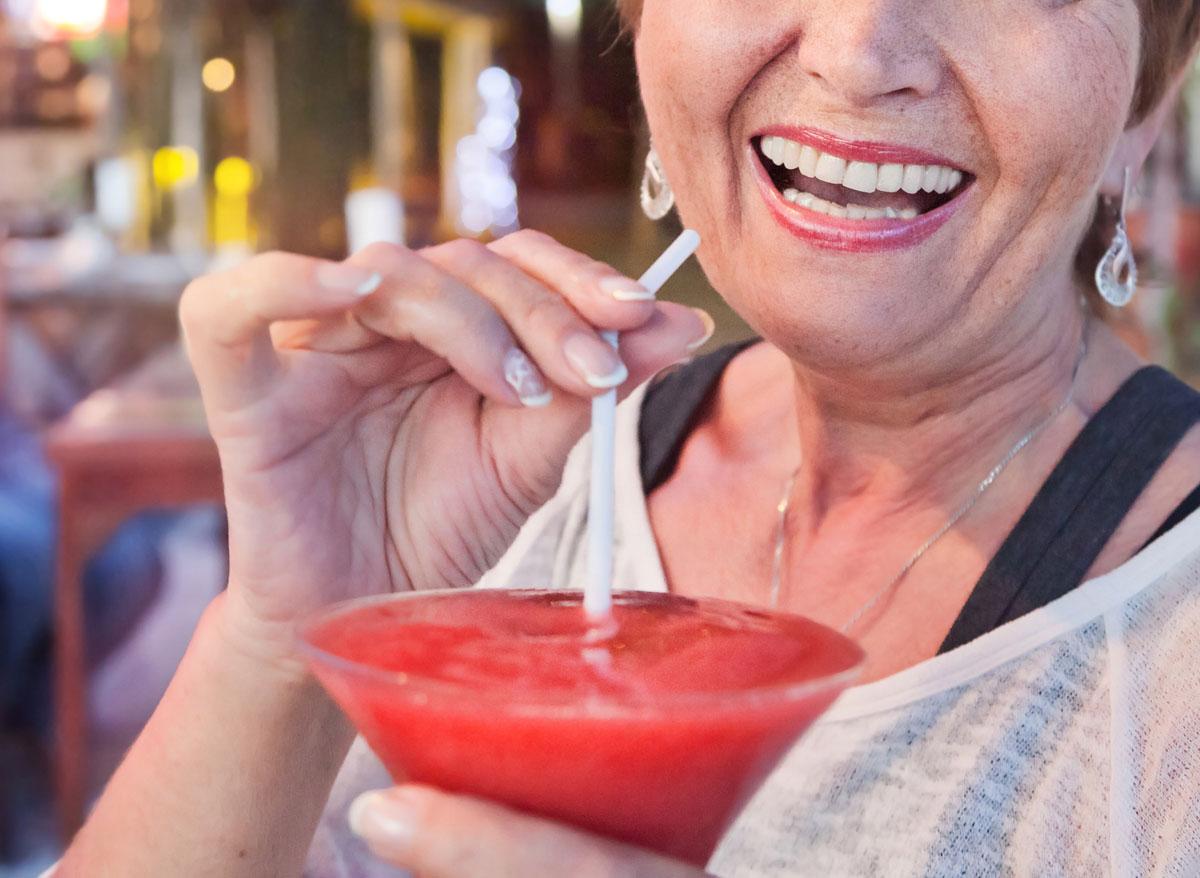 Older woman drinking frozen margarita