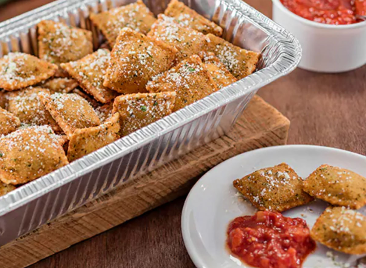 olive garden toasted beef and pork ravioli in serving tray with plate of three ravioli and tomato sauce