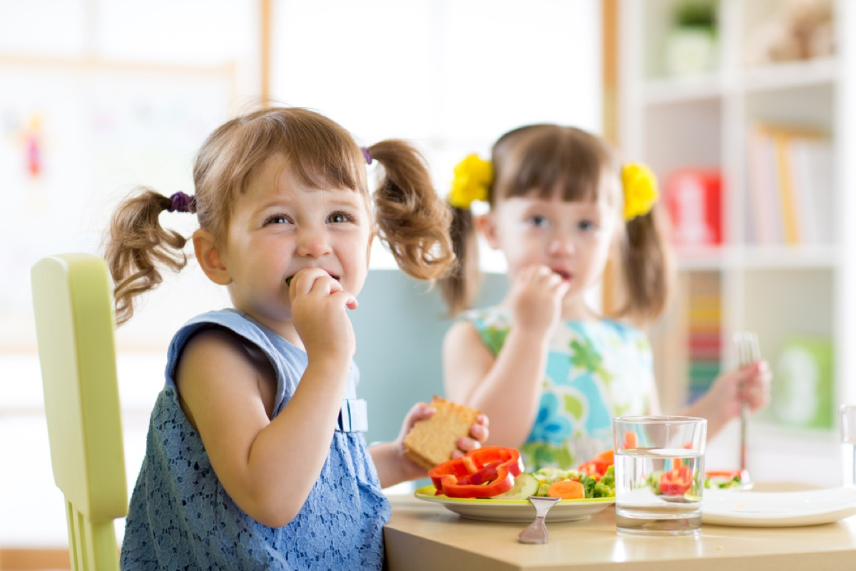young girls with pigtails eating snack at a table, peanut free preschool snacks