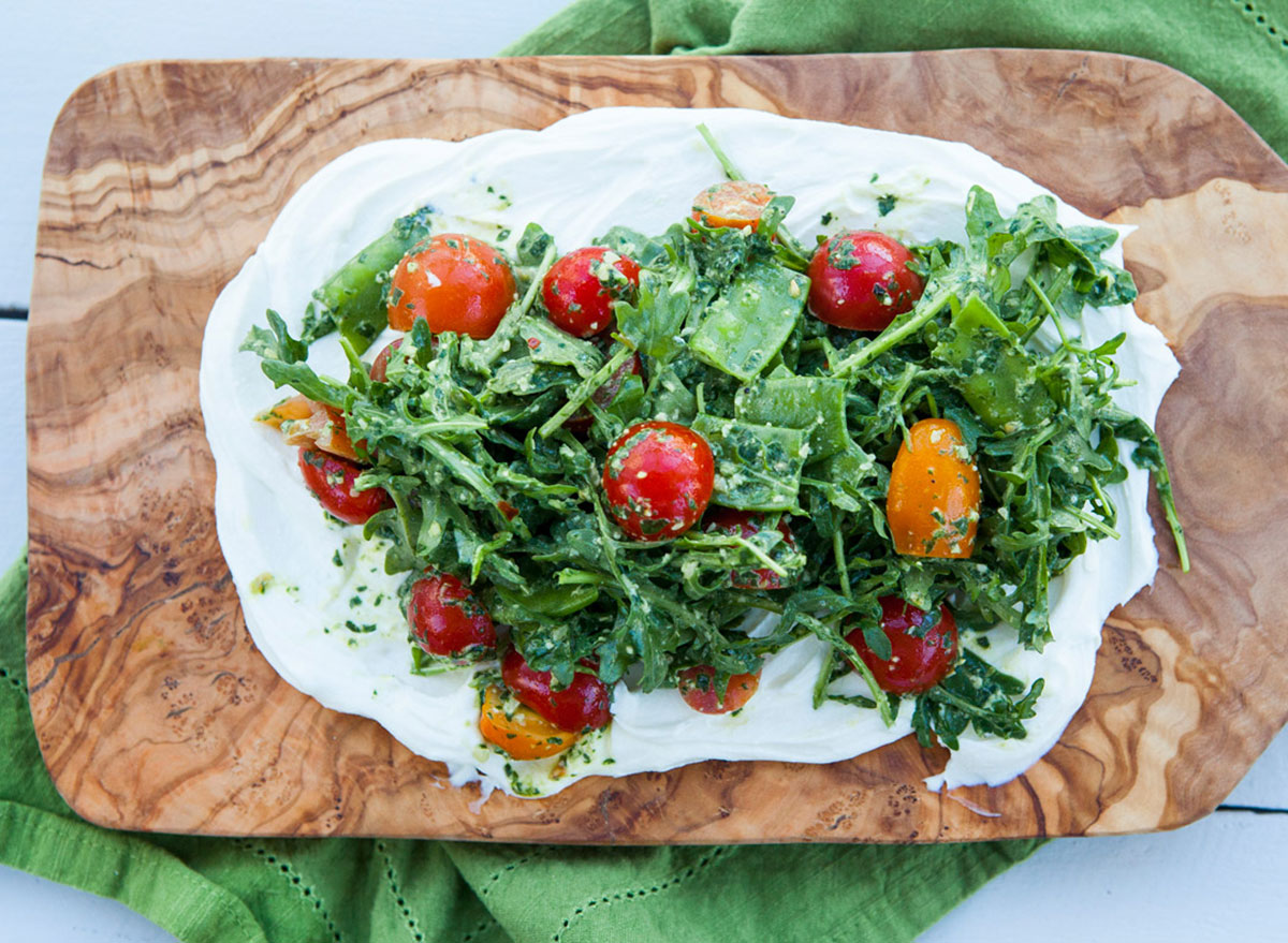 ricotta tomato arugula salad on wooden board with green dish towel healthy with nedi
