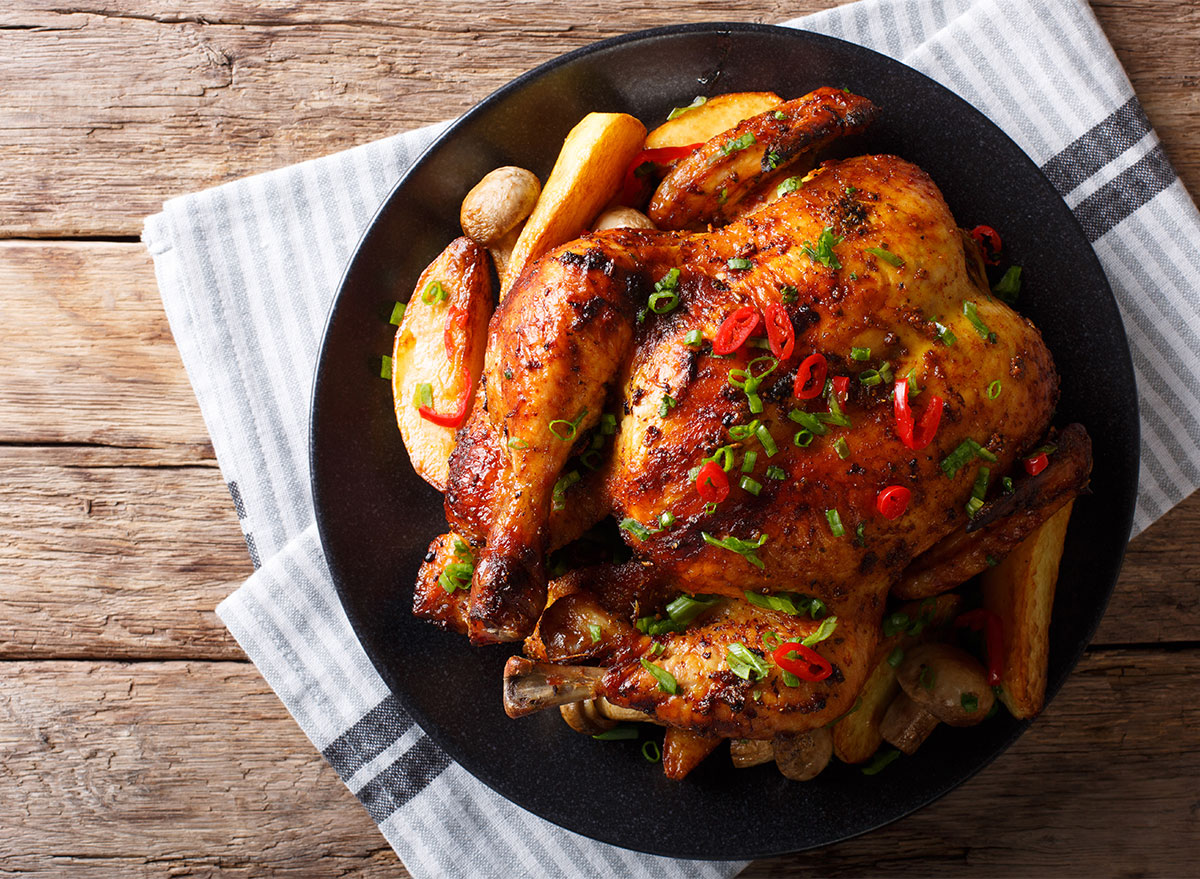 roast chicken with potatoes on black plate