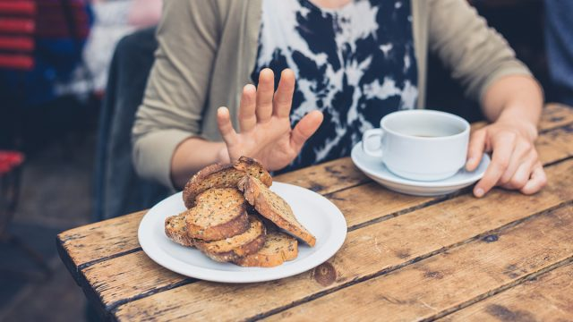 woman refrains from touching a plate of bread
