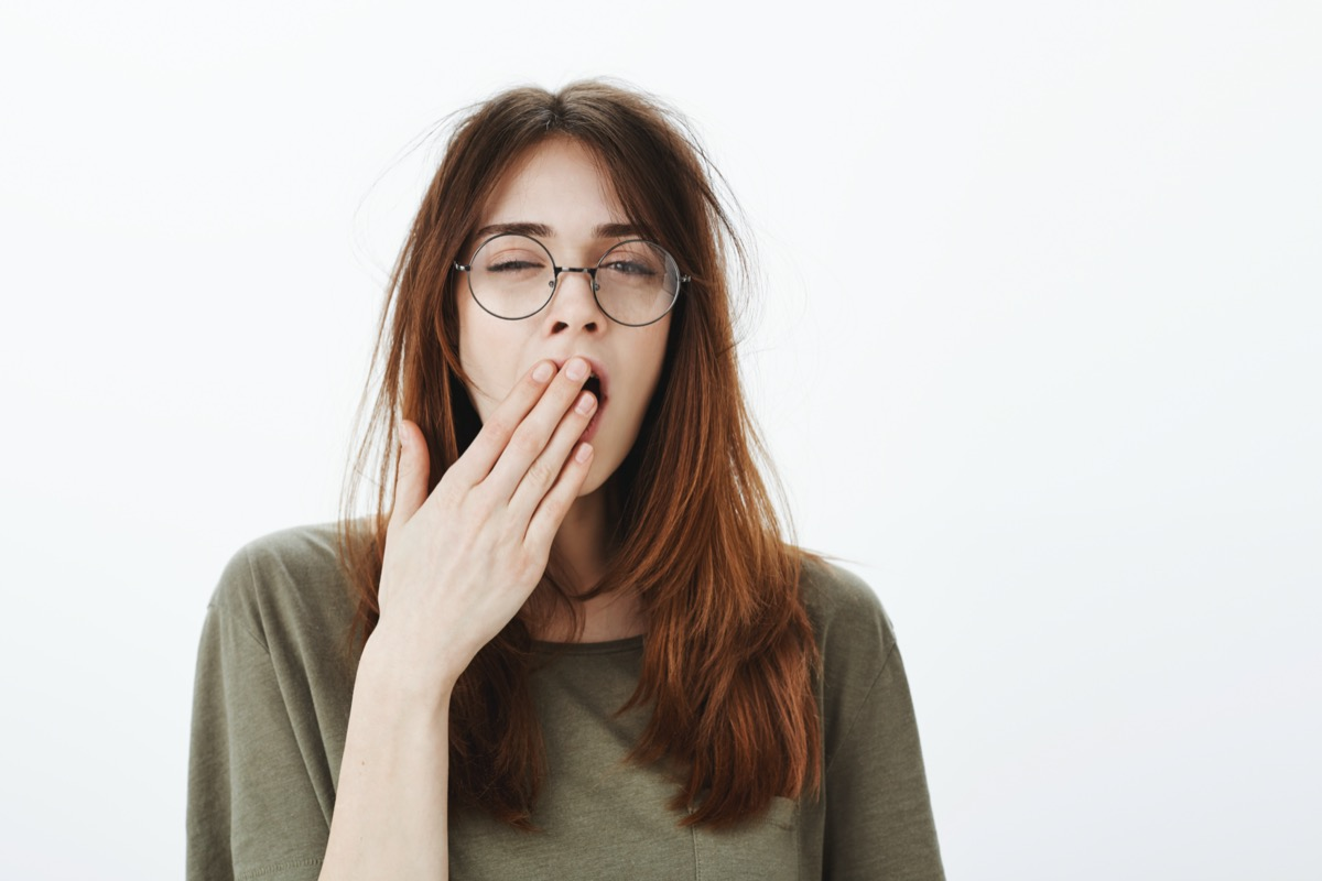 Shot of sleepy woman with messy brown hair, wearing glasses, feeling tired after night without sleep, yawning, covering opened mouth with palm