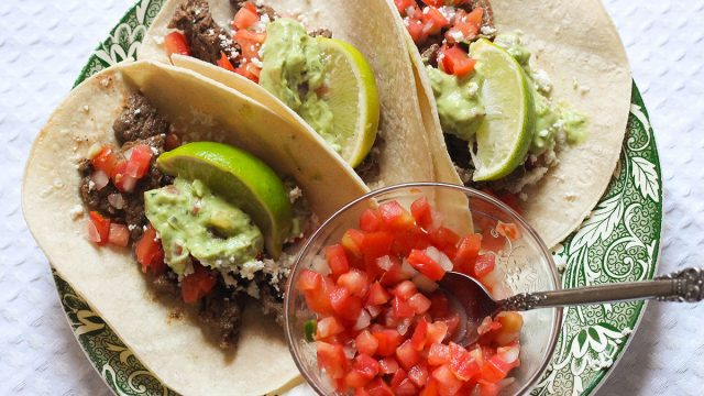 Steak tacos with pico de gallo on a green plate.