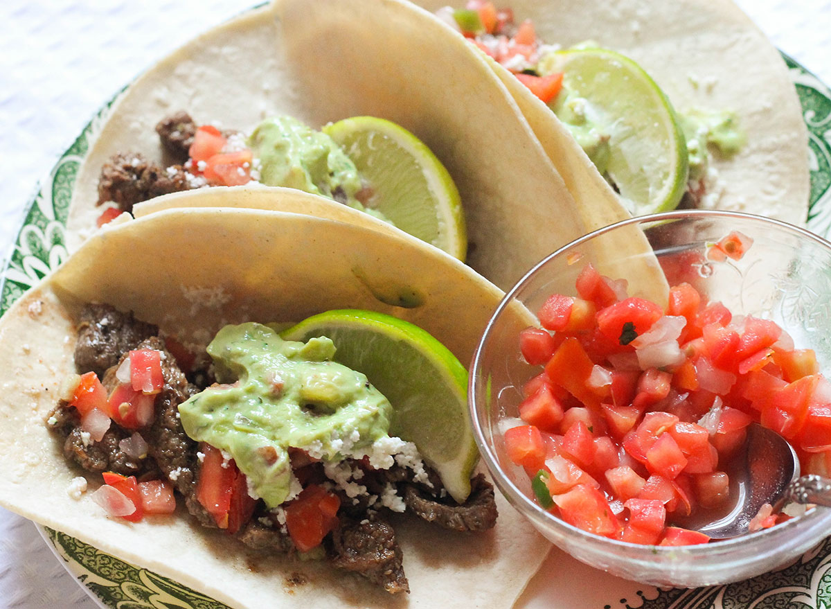 Steak tacos with toppings on a plate.