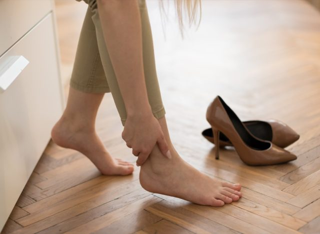 Tired woman touching her ankle, suffering from leg pain because of uncomfortable shoes, feet pain wear high heel shoes