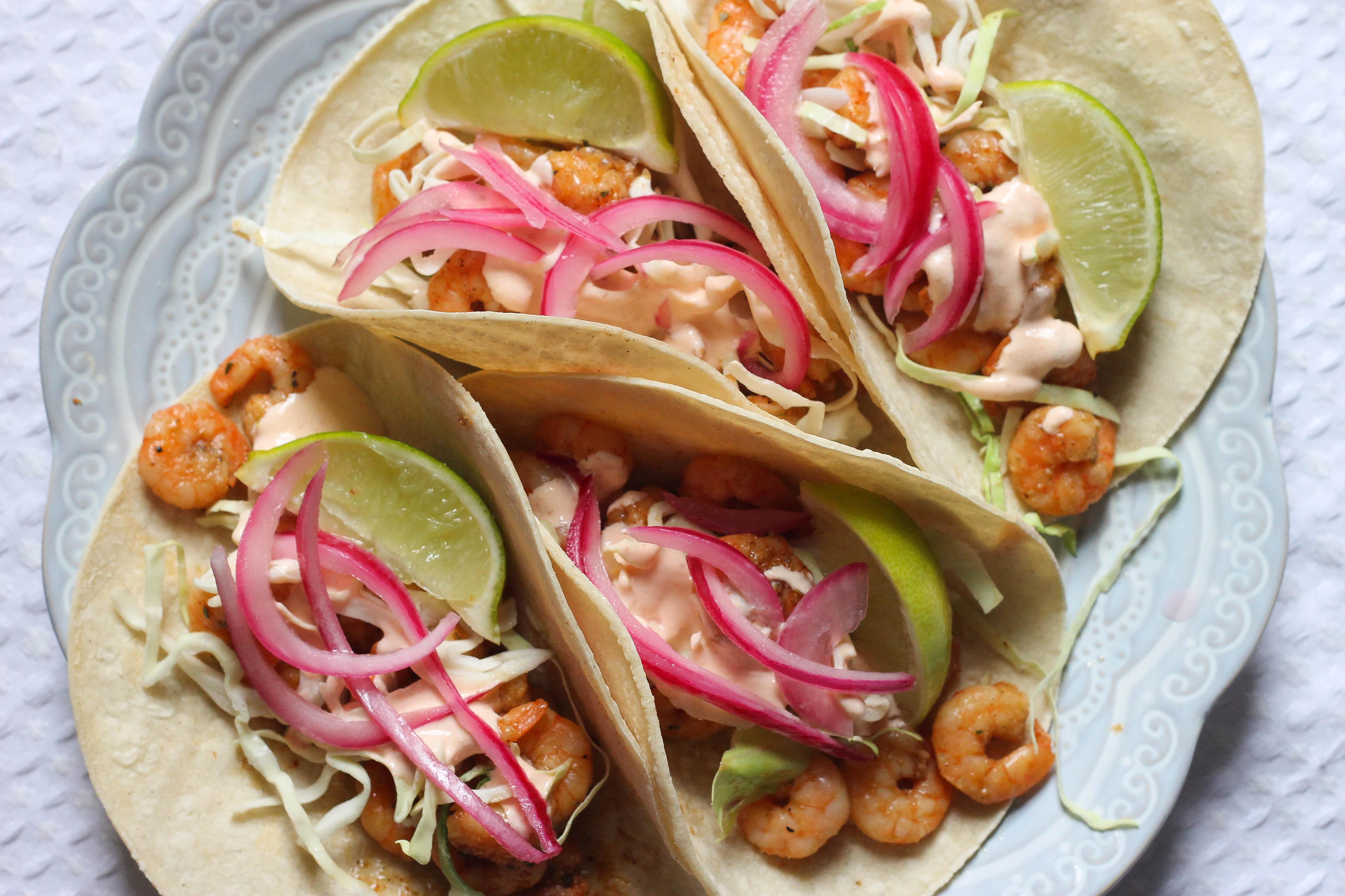 four shrimp tacos on a blue plate