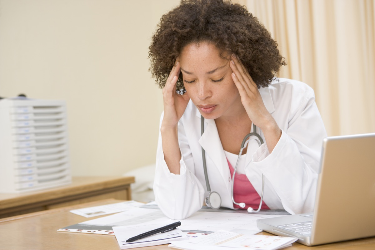 Doctor with laptop and headache in doctor's office
