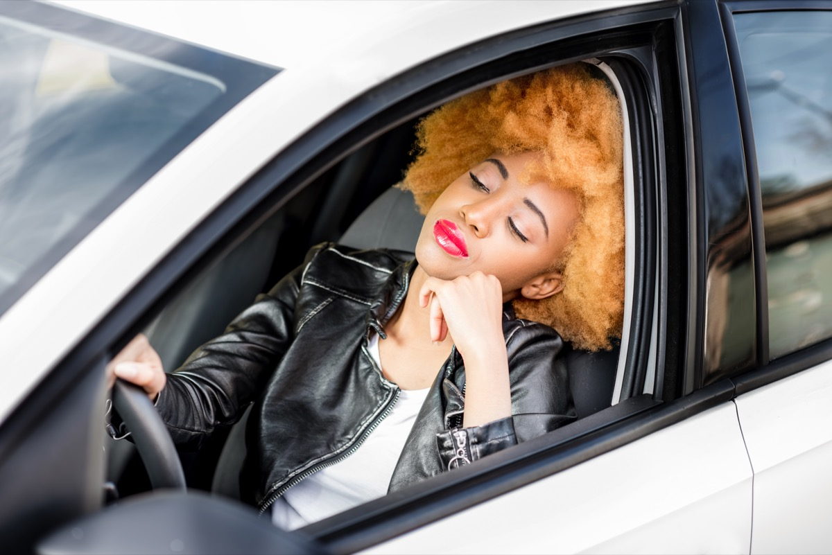 african woman in leather jacket feeling sleepy while driving the car