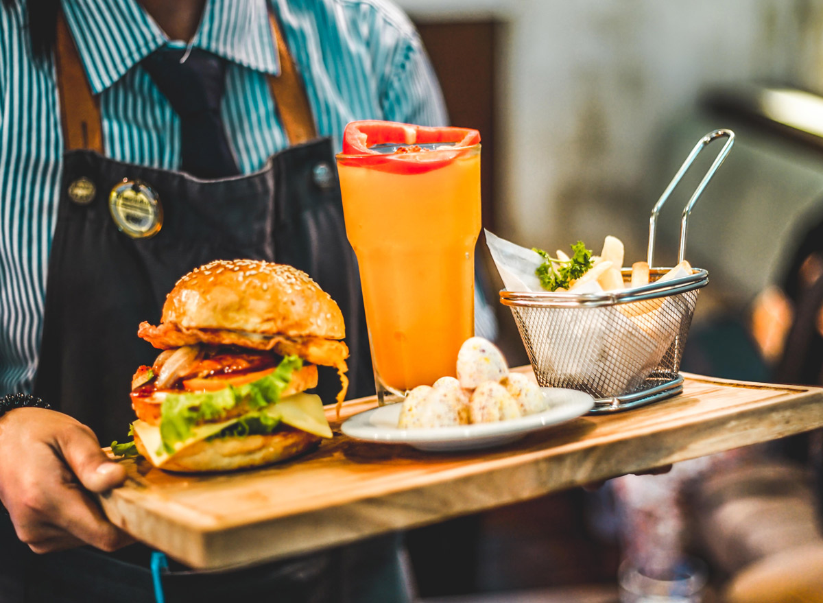waiter with tray of burger and beer