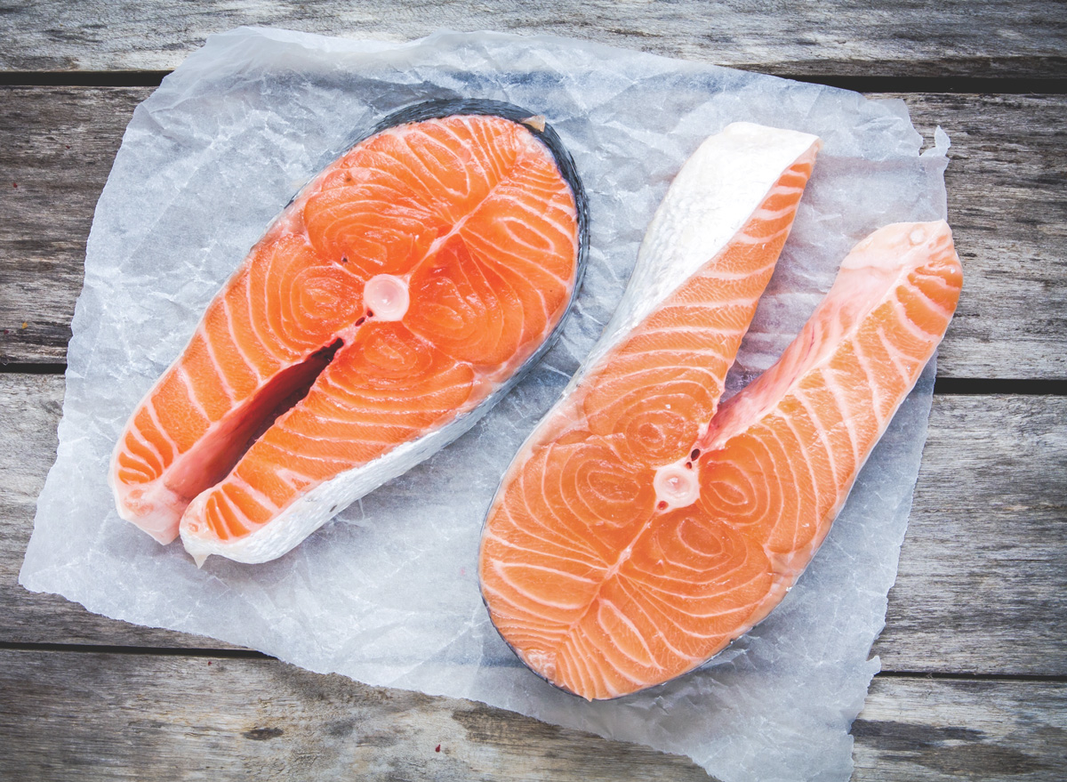 wild vs farmed salmon raw fillets on parchment paper