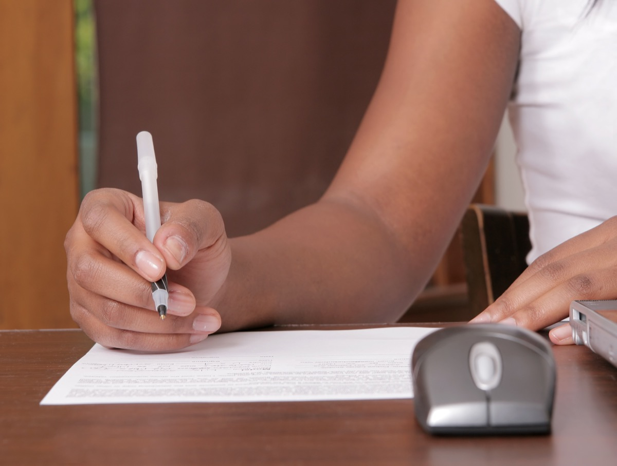 woman writing on a piece of paper near a workstation