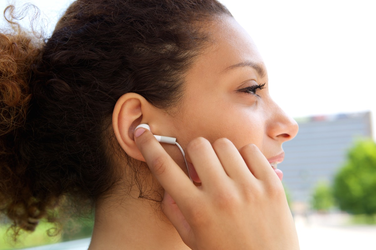 woman listening to music with earphones in ears