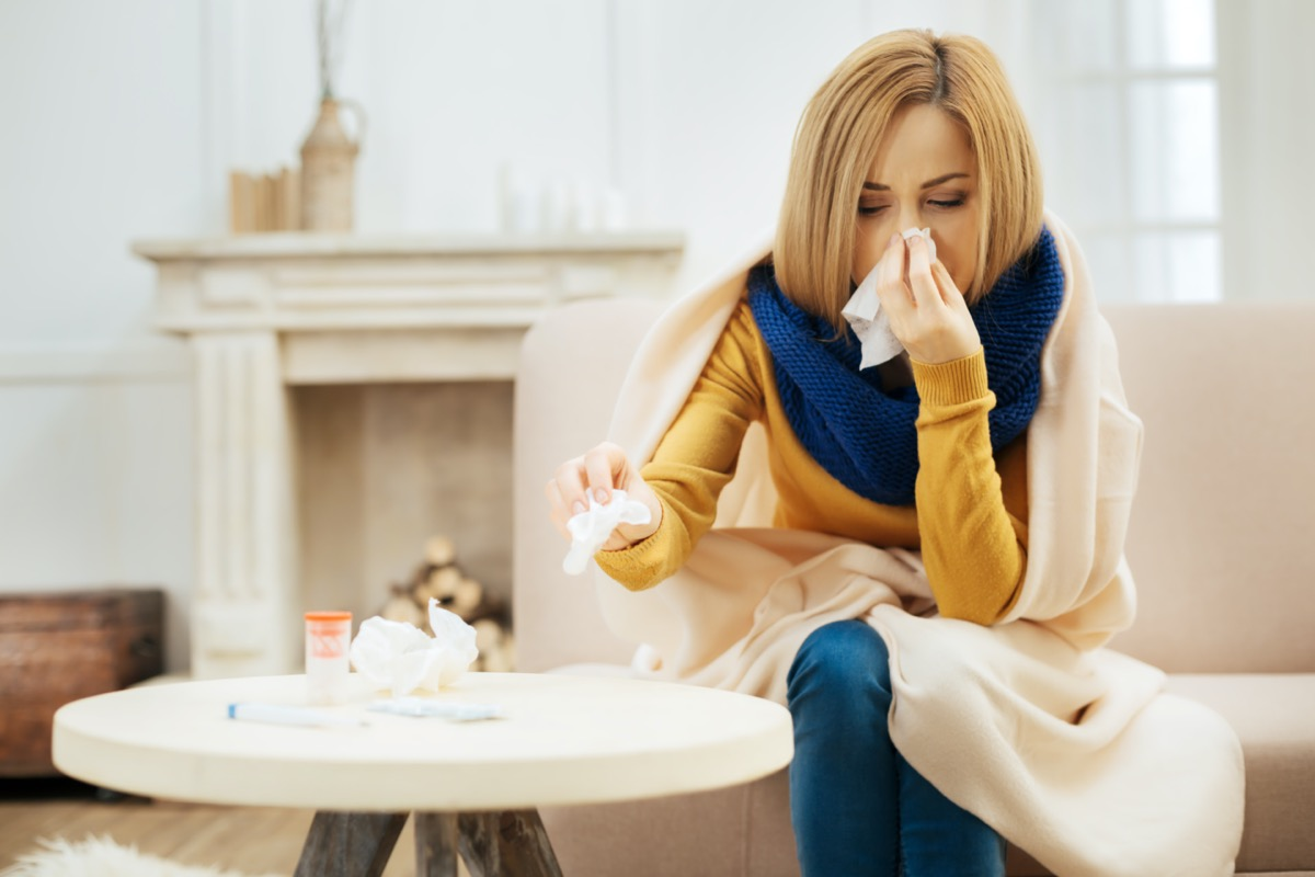 Ill young blond woman having fever and blowing her nose while having a blanket on her shoulders and sitting on the couch with her eyes closed and table with pills in front of her
