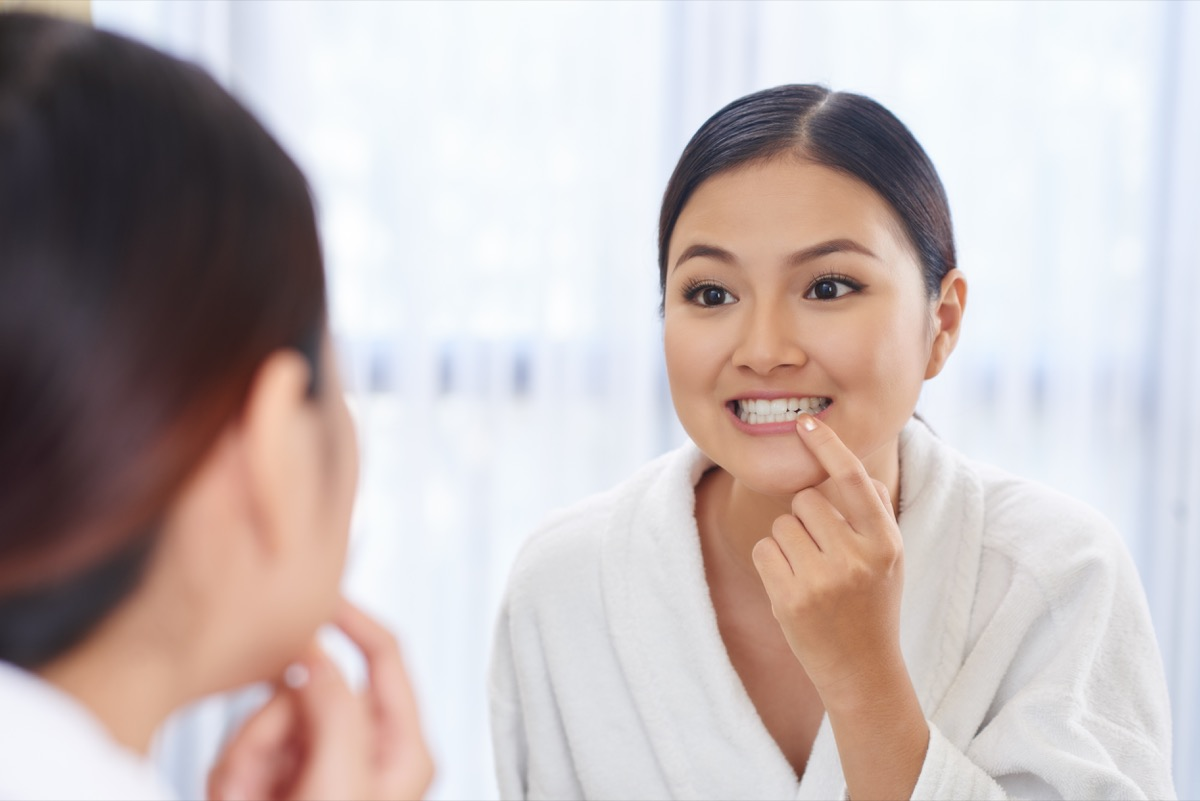 woman looking at her teeth in the mirror