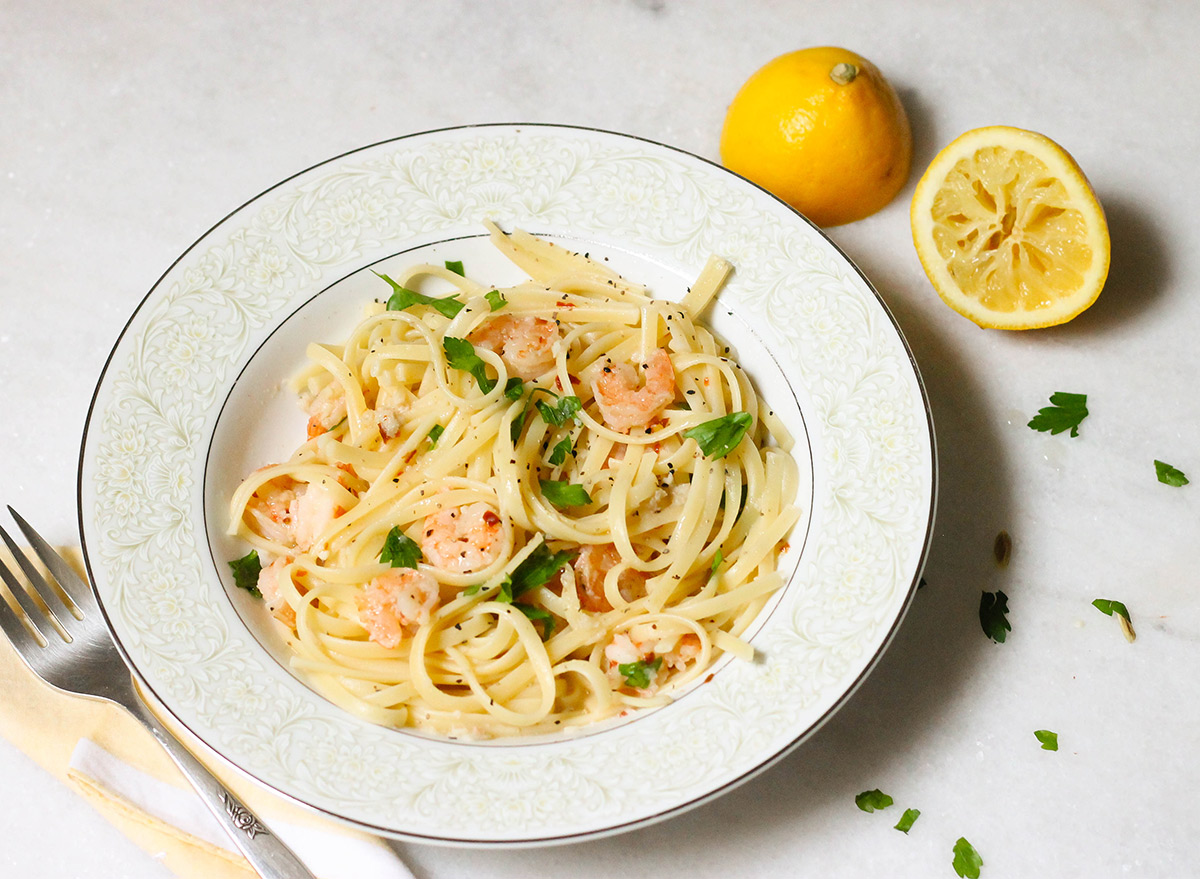 Garlic shrimp scampi recipe with linguine on a marble counter with squeezed lemon