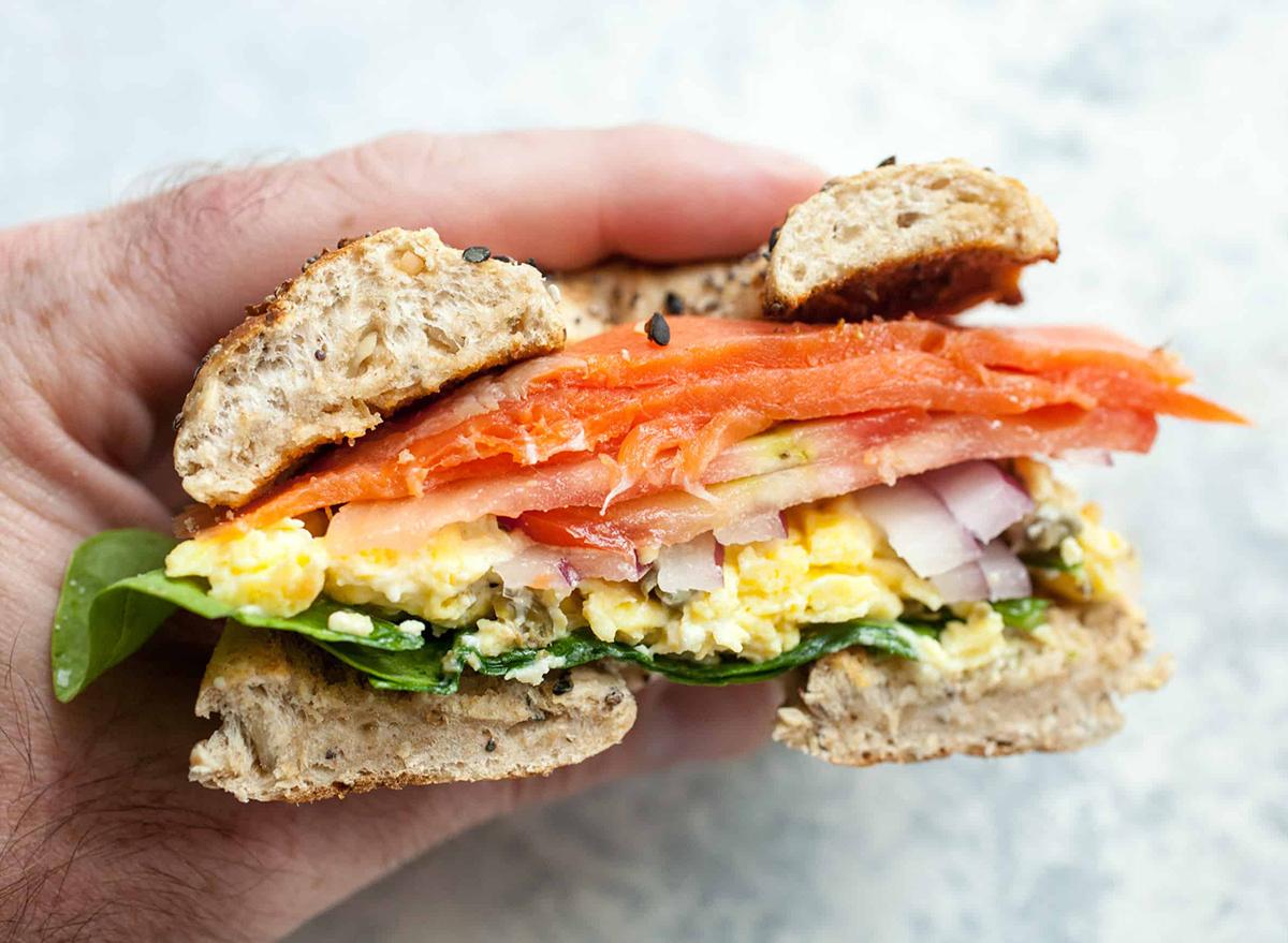 Lox breakfast bagel sandwich in hand cut in half