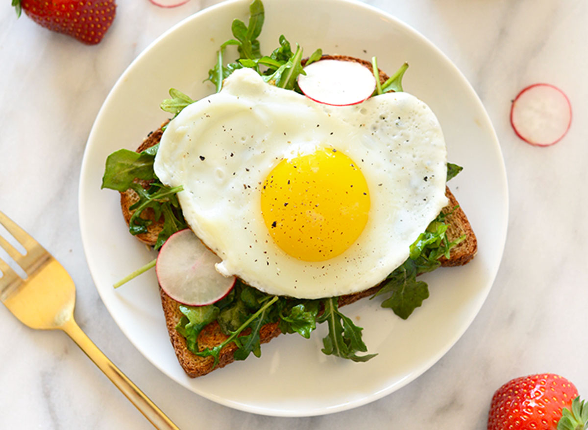 Open face breakfast toast with egg and arugula