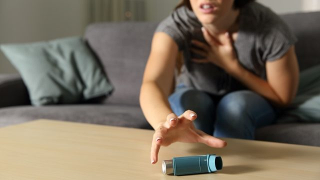 Asmathic girl catching inhaler having an asthma attack