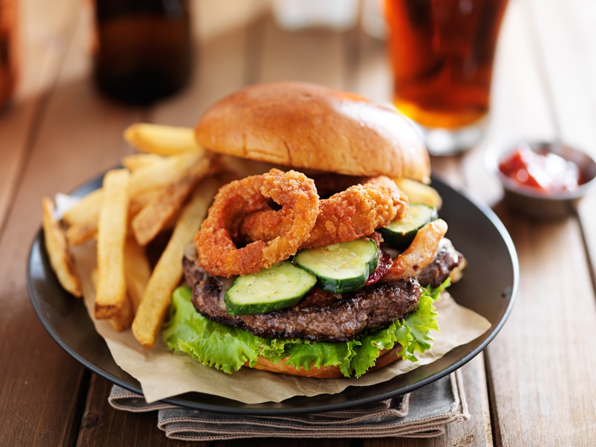 big cheeseburger loaded with onion rings, bacon and bbq sauce served with fries