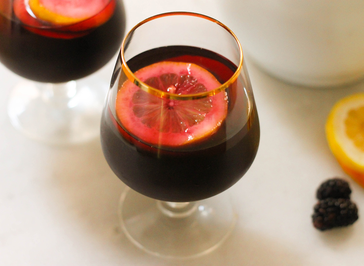 Cup of homemade blackberry sangria with slices of lemon and oranges