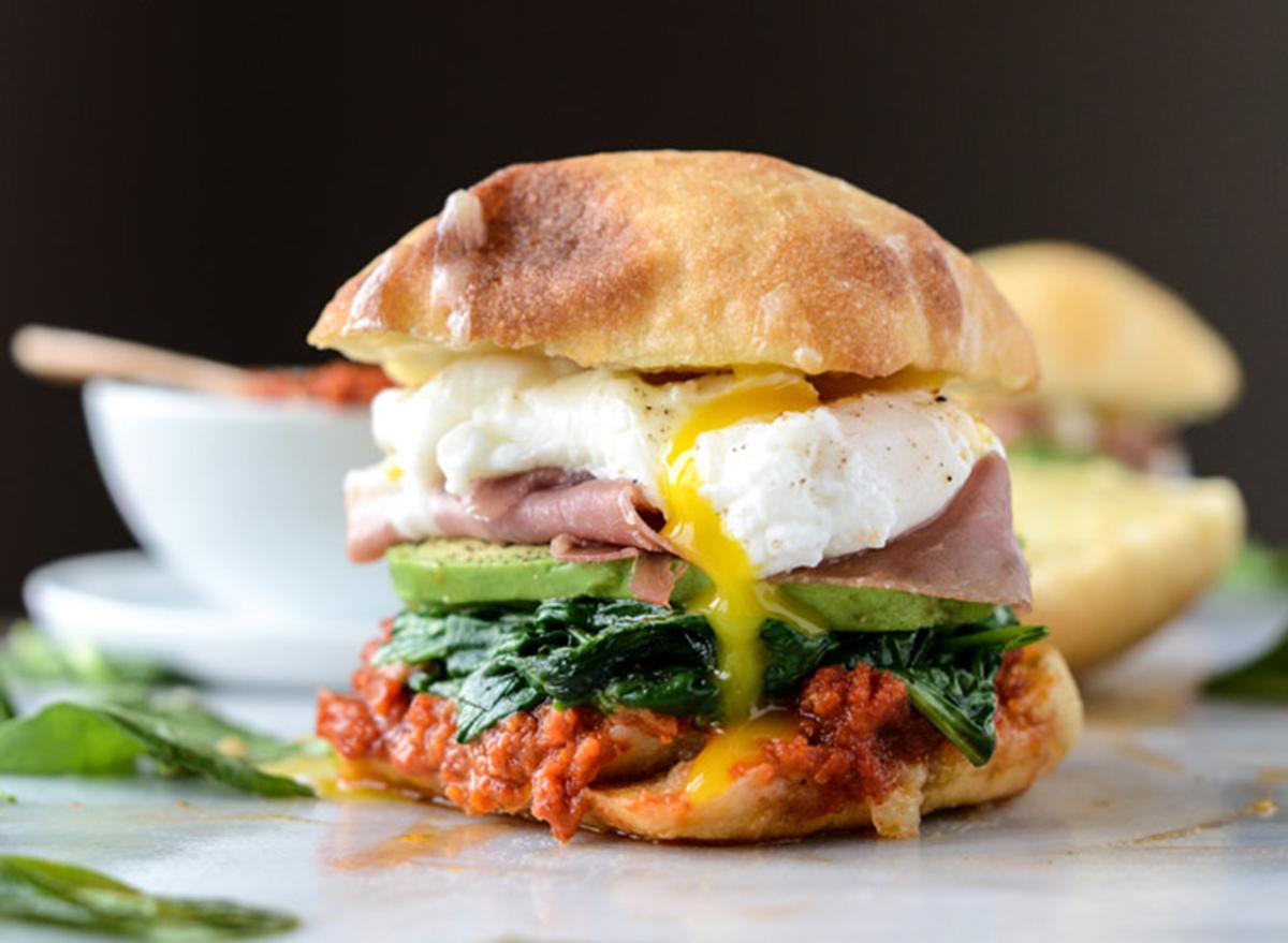 Breakfast sandwich with egg, ham, avocado on a ciabatta roll.