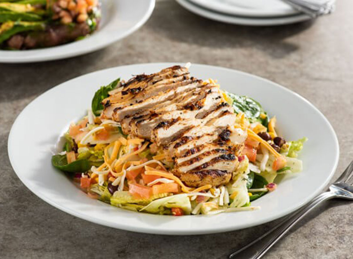 chilis grilled chicken salad in a white bowl