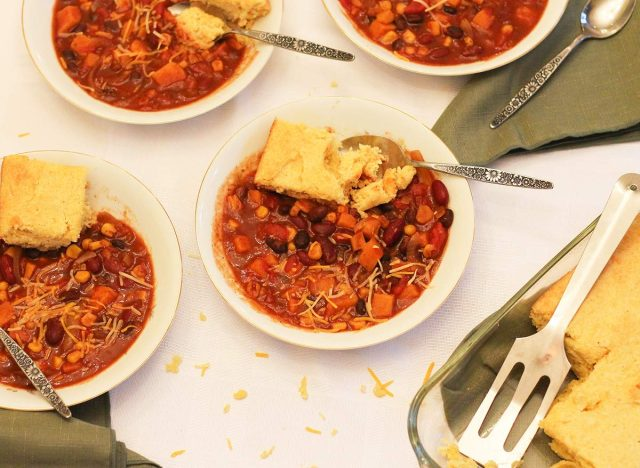 Crock pot vegetarian chili recipe with cheese and cornbread for the table