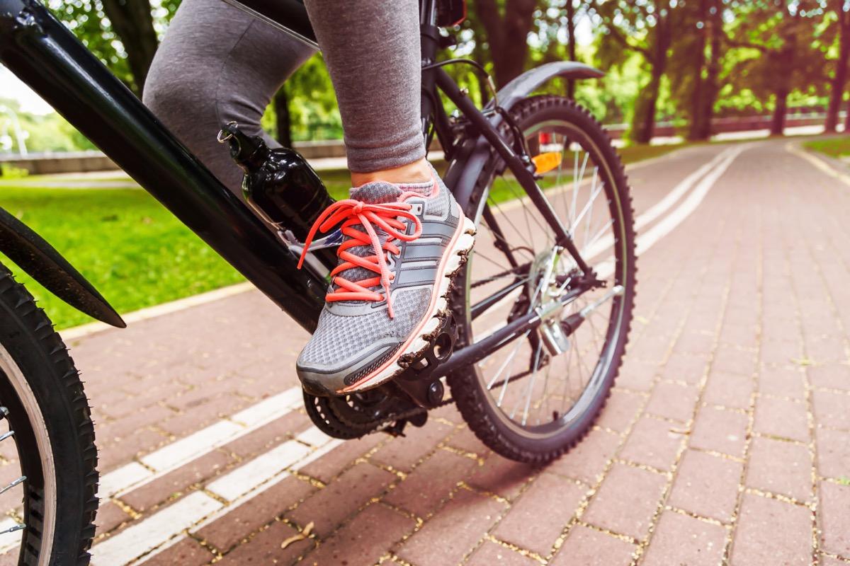 cyclist woman feet riding mountain bike on trail