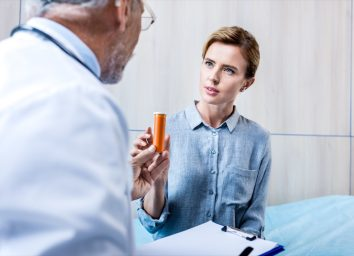 male doctor with clipboard giving pills to female patient in hospital room