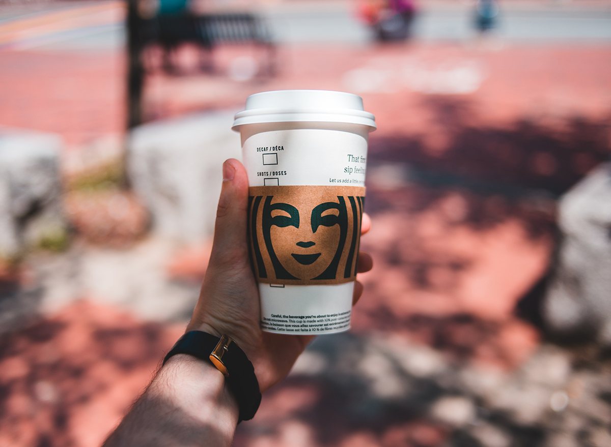 Man holding Starbucks cup outside