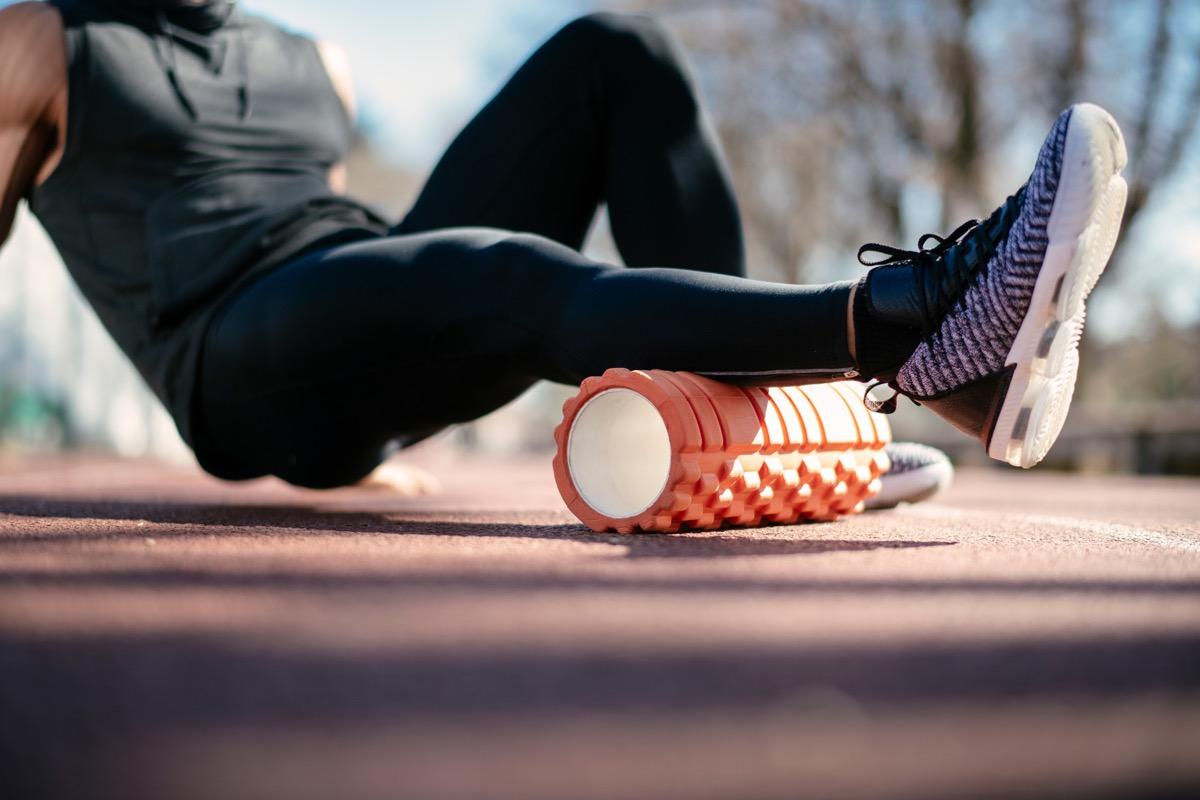 Man foam rolling. Athlete stretches using foam roller