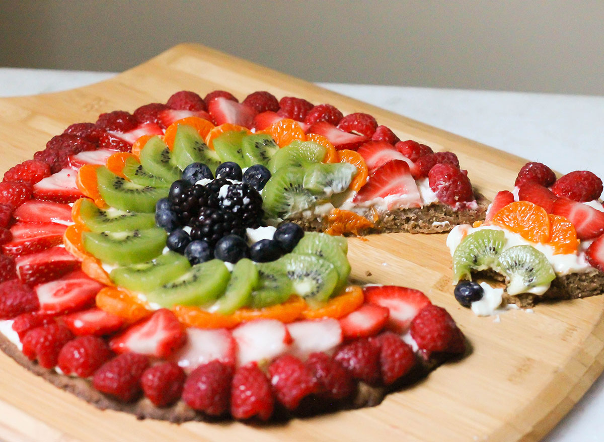 Slicing up a sugar cookie fruit pizza on a wooden pizza pan