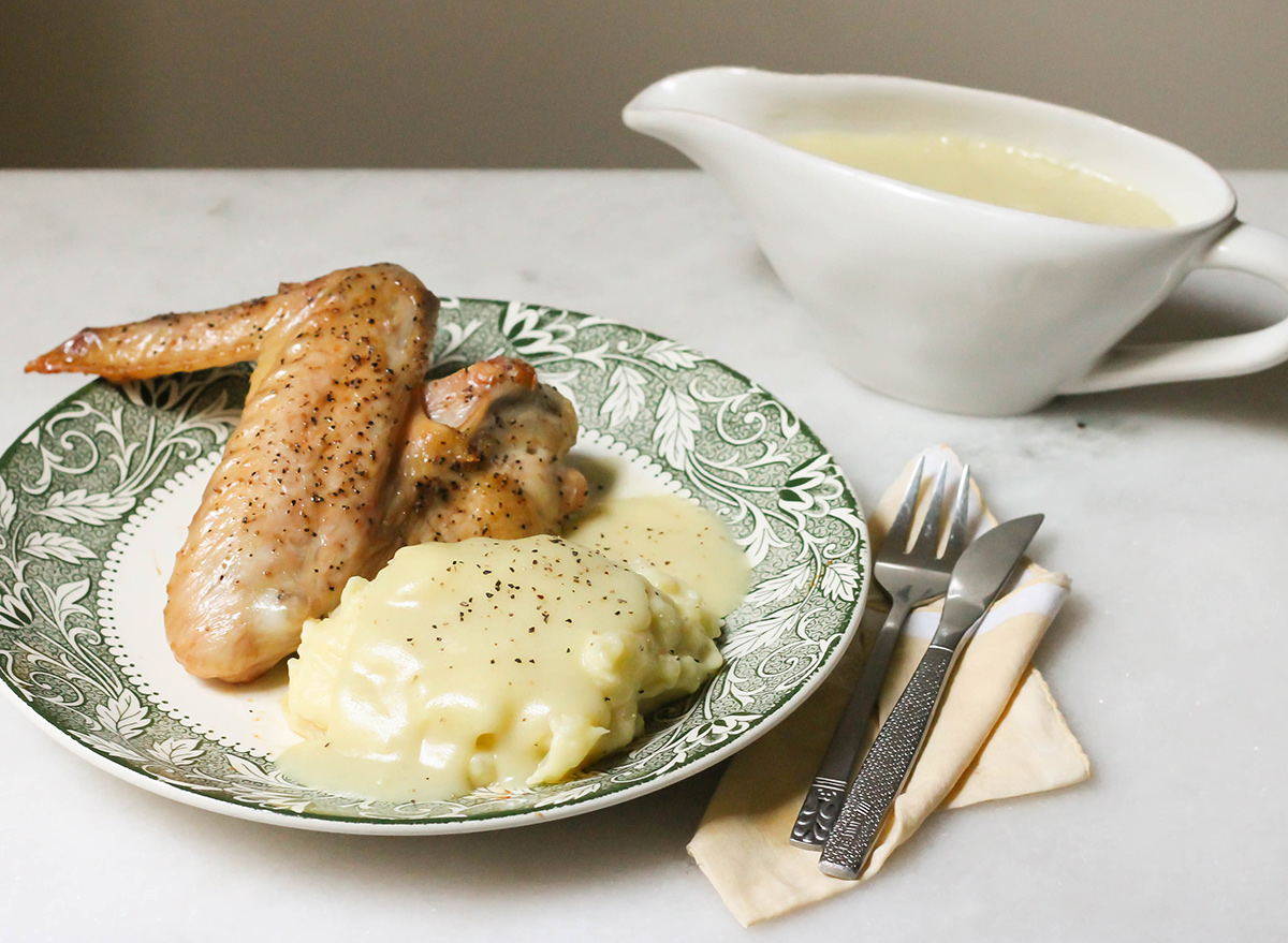 Homemade gravy in a boat with turkey wing and mashed potatoes seasoned