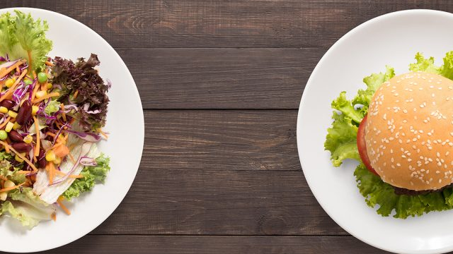 a salad sits next to a burger on a wooden table