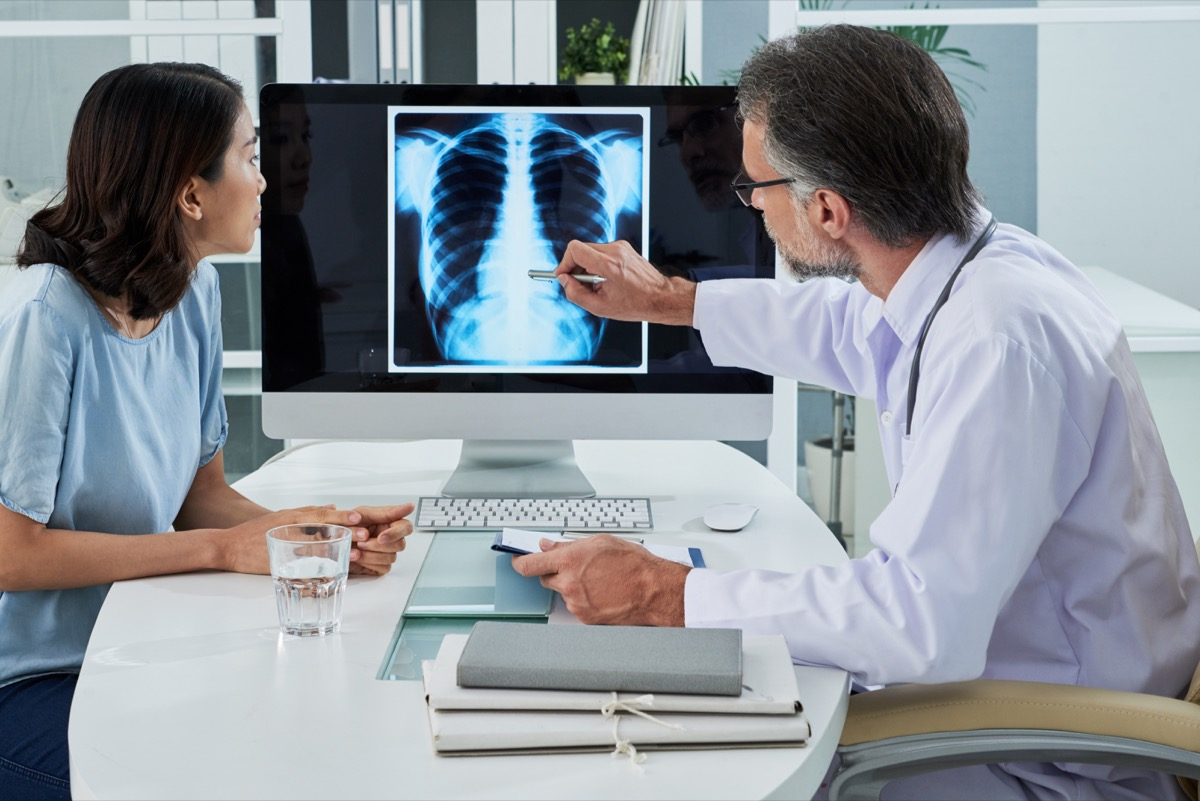 Doctor explaining lungs x-ray on computer screen to patient