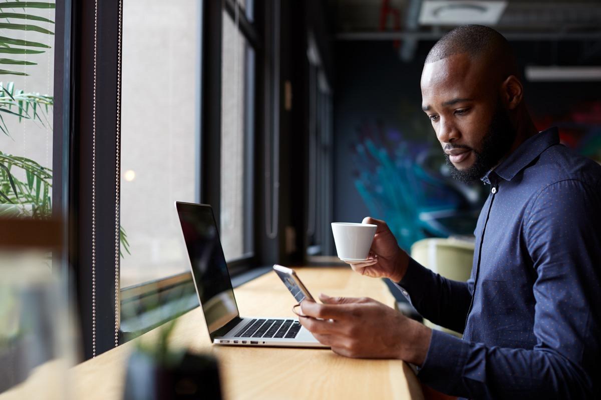 male creative sits by window having coffee