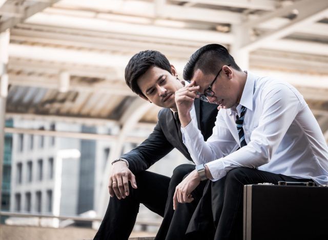 Frustrated Asian young business man sitting outdoor office