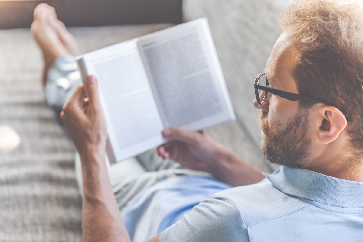Man in casual clothes and eyeglasses reading a book while lying on couch at home