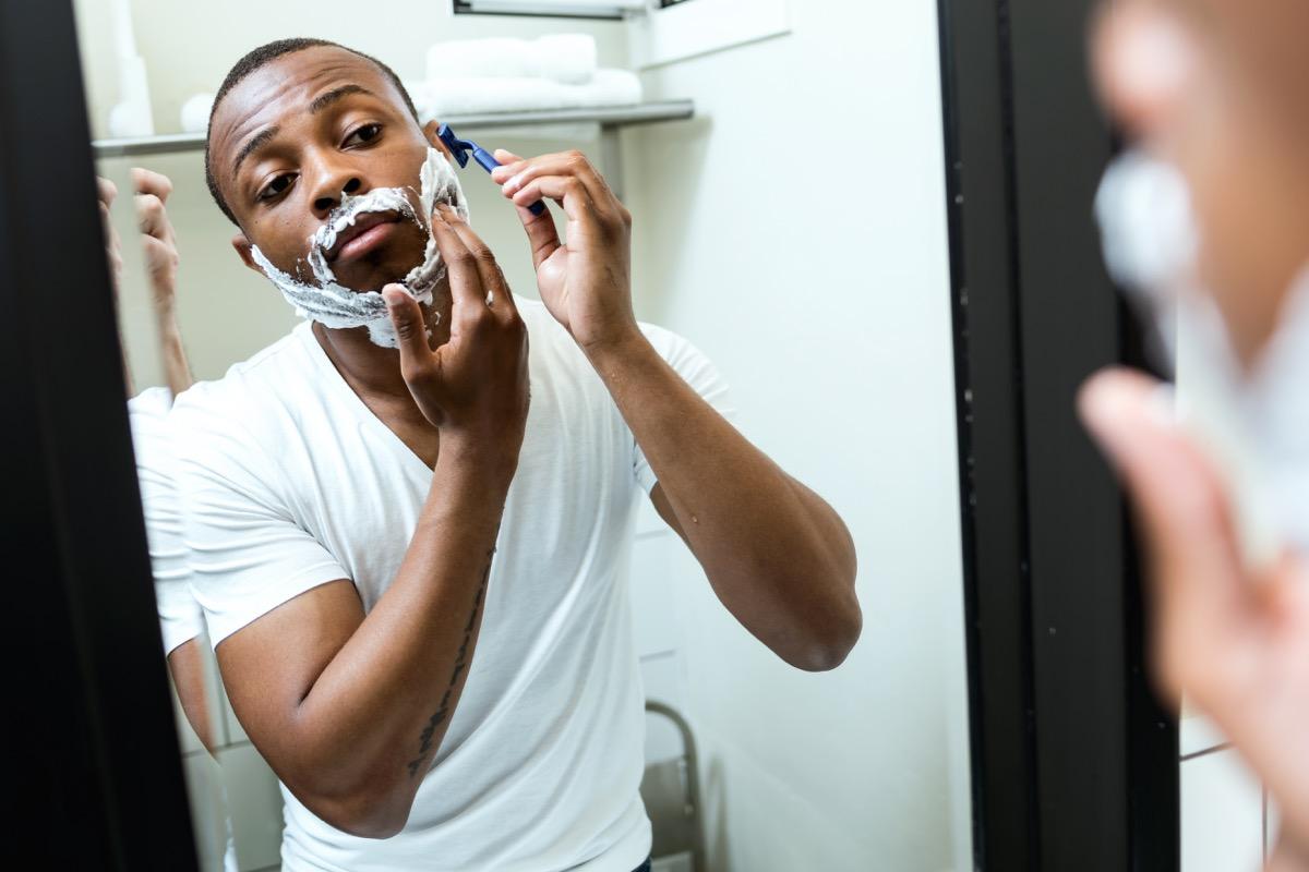 black man shaving in home bathroom