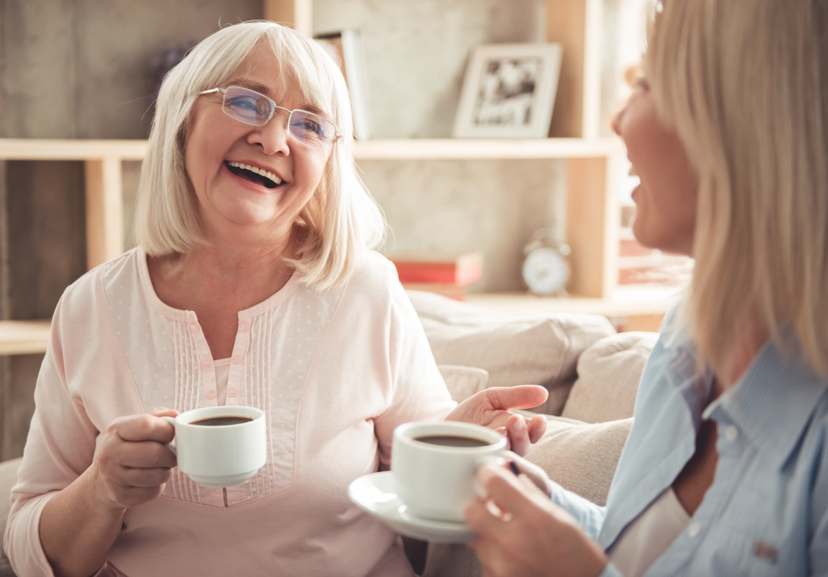 mature mother and her adult daughter are drinking coffee